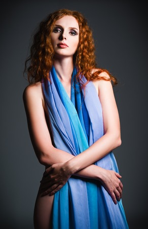 Studio portrait of a beautiful young red-haired woman covered in cloth  photo