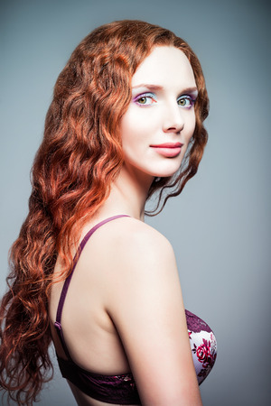 Closeup studio portrait of a pretty redhead woman  Half-turned    photo