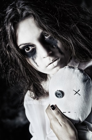 Horror shot: the sad strange girl with moppet doll in hands. Closeup portrait Stock Photo