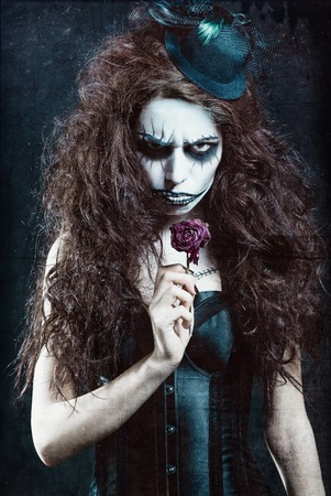 freaky: Woman in image of a gothic freak clown with withered flower. Grunge texture effect Stock Photo