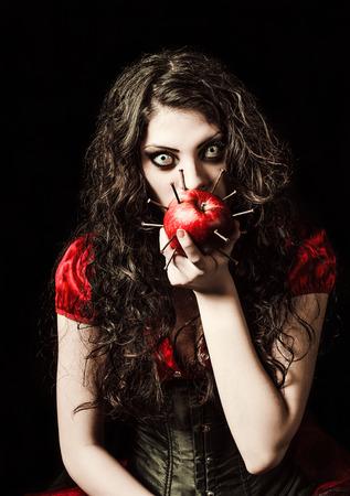freaks: Horror shot: the strange scary girl eats apple studded with nails