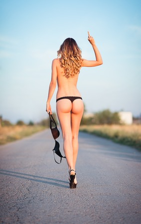 Sexy young woman in lingerie going by the road and showing offensive gesture (middle finger). Rear view photo
