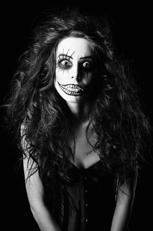 Beautiful young woman in the image of a sad gothic freak clown. Black and white photo