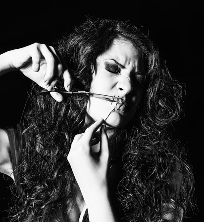 freaks: Horror shot: strange girl with mouth sewn shut cutting the thread. Monochrome Stock Photo