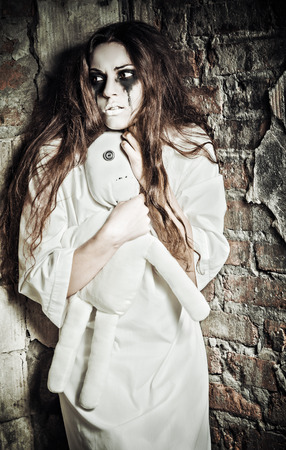Horror scene: the strange crazy girl with moppet doll in hands