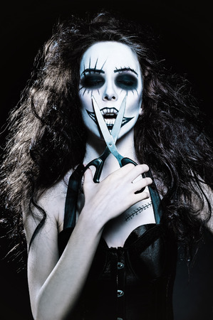 Young woman in the image of a sad gothic freak clown with scissors in hand photo