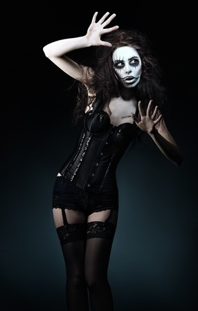 Beautiful young woman in the image of a sad gothic freak clown photo