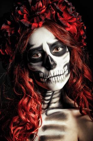 Closeup portrait of a sad young girl with muertos makeup (sugar skull) photo