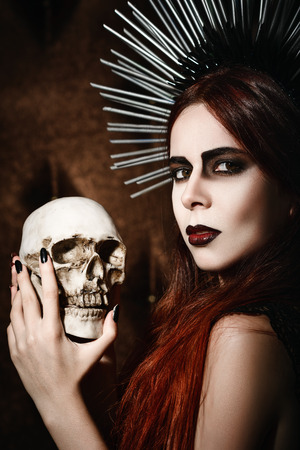 necromancer: Portrait of a beautiful gothic girl holding the skull Stock Photo