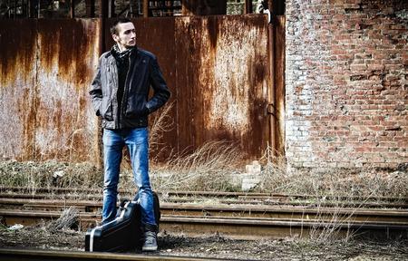 guitar case: Hombre joven con la caja de la guitarra a la espera de que el tren entre las ruinas industriales