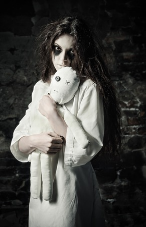 Horror shot: the sad strange girl with moppet doll in hands