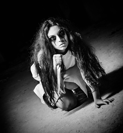 woman knife: Horror shot: a scary monster girl with knife in hands. Black and white Stock Photo