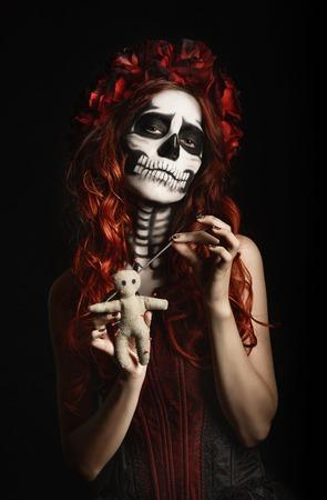 Young woman with calavera makeup (sugar skull) piercing a voodoo doll photo