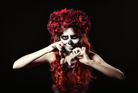 Young voodoo witch with muertos makeup (sugar skull) piercing a doll photo