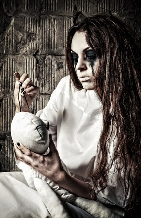 Horror scene: the strange crazy girl with moppet doll and needle in hands 스톡 콘텐츠
