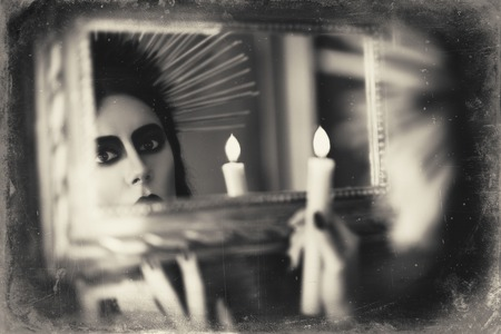 goth girl: Beautiful goth girl holding candle in hand and looking into the mirror. Grunge texture effect