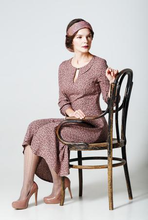 素敵な若い女性が椅子に座っています。レトロなスタイルの肖像画