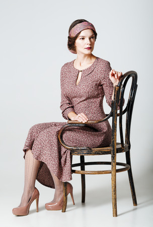 vestidos antiguos: Encantadora joven sentado en una silla. Retrato en estilo retro Foto de archivo