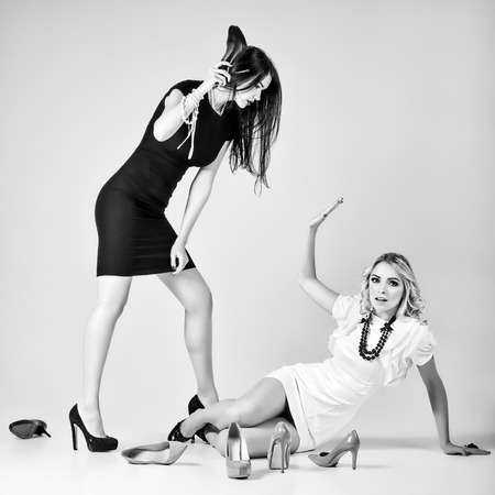 bitch: Studio fashion shot: the battle of two beautiful women (blonde and brunette). Black and white Stock Photo