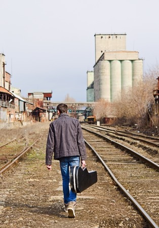 guitar case: A young man with guitar case in hand going away by rails. Rear view
