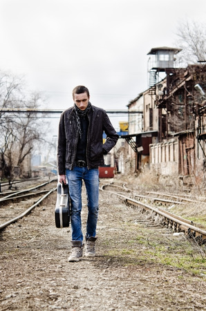 hand rails: Sad lonely young man with guitar case in hand going by the rails Stock Photo