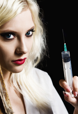 nurse injection: Beautiful young girl in the image of nurse with syringe in hand. Closeup