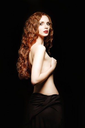Studio portrait of a sexy ginger woman on black background. Half-turned photo