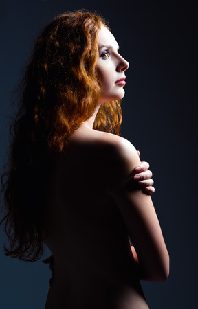 women face stare: Studio portrait of a beautiful ginger woman. Profile view Stock Photo