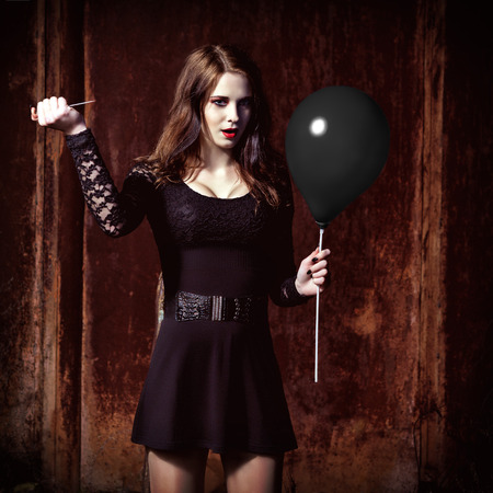 gothic woman: A weird angry girl is piercing a black balloon by needle