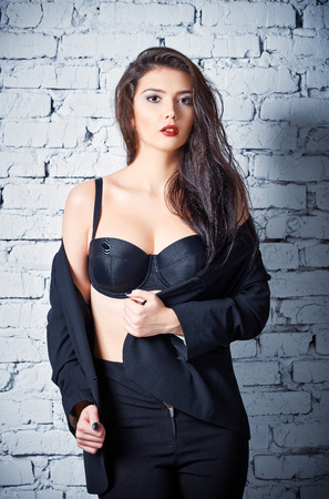 black bra: Fashion shot: a beautiful young woman in pants and jacket stands at the wall