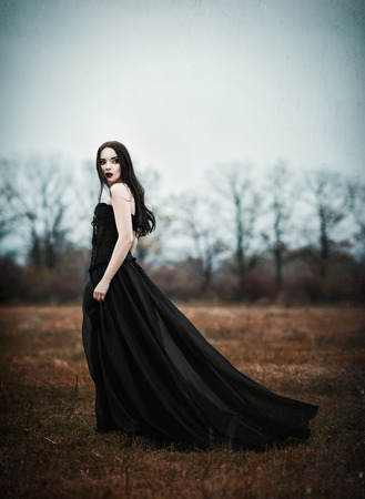 A beautiful sad goth girl stands in autumnal field. Grunge texture effect