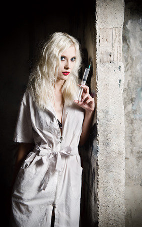 Beautiful young girl in the image of nurse with syringe in hand standing by the wall photo