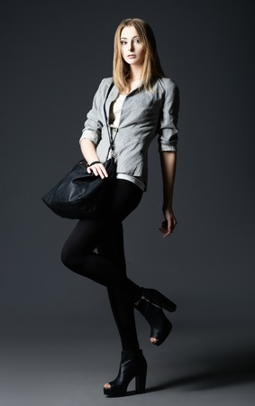 Studio fashion shot: a beautiful young woman in leggings and jacket, with bag in hand