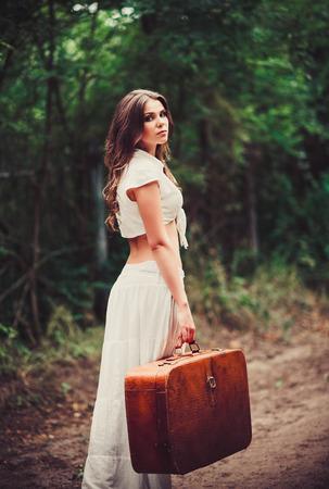 femme valise: Belle jeune femme triste avec une valise à la main, debout sur une route