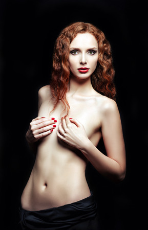 Studio portrait of a sexy red-haired woman on black background photo