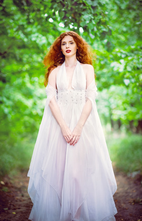 red haired: Cute red-haired woman wearing white dress in the garden