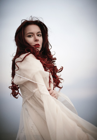 beautiful redhead: Portrait of a beautiful sad young woman in white dress