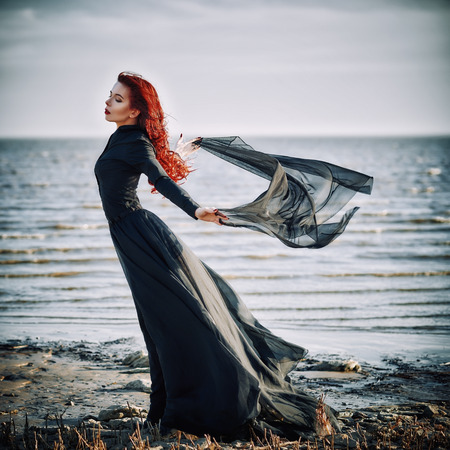 Beautiful sad goth girl with cloth in hands standing on the sea shore Stock Photo