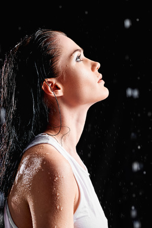 women face stare: Portrait of beautiful young woman in a water studio. Profile view Stock Photo