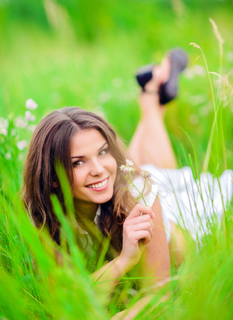 Happy smiling beautiful young girl lying among the grass and flowers photo