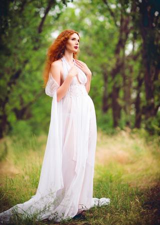 Beautiful ginger woman wearing white dress in the garden photo