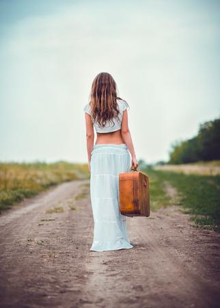 フィールド道路で離れて行く手にスーツケースを持つ若い女性 写真素材