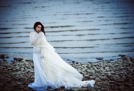 白いドレスを踏んで海海岸で美しい少女は悲しい