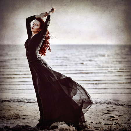 goth girl: Beautiful goth girl standing on the sea coast. Grunge texture effect Stock Photo