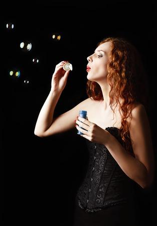 A beautiful redhead girl blows bubbles. Studio portrait, profile view photo