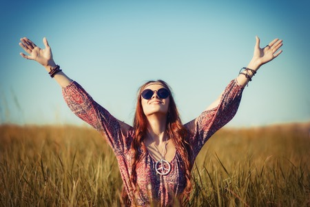 Beautiful young hippie woman sitting in the field and praying to God
