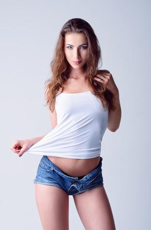 shorts: Disparo de moda: una hermosa joven sonriente en pantalones cortos de mezclilla y camisa