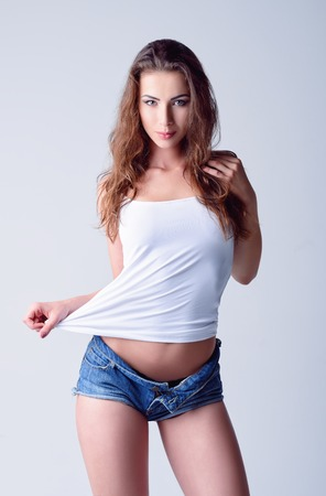white singlet: Fashion shot: a beautiful young smiling girl in denim shorts and shirt Stock Photo