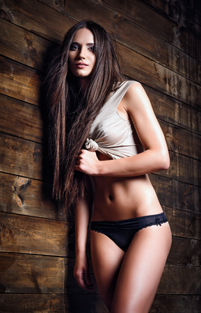 Fashion shot: a beautiful girl in panties and shirt stands at the wood wall