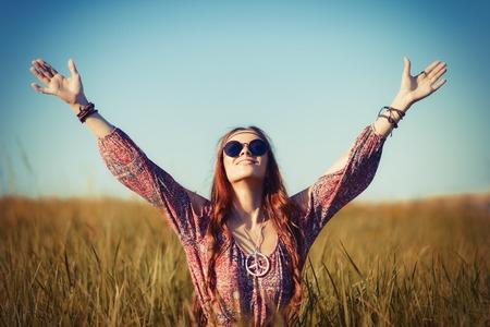 mujer hippie: Hermosa mujer hippie joven sentado en el campo y orando a Dios